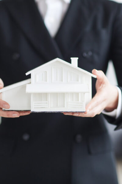 Close-up of real estate agent in black suit holding model of the house in her hands